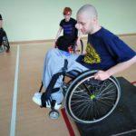 Na sali gimnastycznej młody chłopak siedzący na wózku inwalidzkim zjeżdża z niskiej przeszkody imitującej krawężnik. W tle dwie inne osoby na wózku przyglądają się tej czynności.